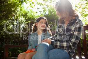 Girl sitting with mother on wooden bench against trees during sunny day