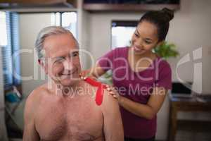 Female therapist applying elastic therapeutic tape on shoulder of smiling shirtless senior male pati