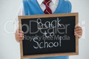 Schoolboy holding writing slate with text back to school against white background