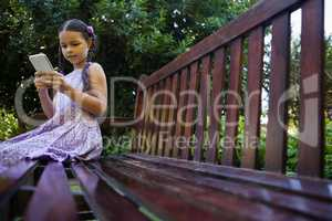 Surface level of girl sitting on wooden bench while using mobile phone