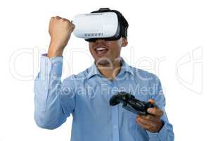 Happy businessman with vr glasses clenching fist while playing video game