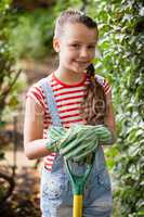 Portrait of smiling girl standing with gardening fork