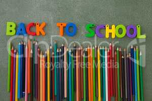 Block letters and color pencils arranged on chalkboard