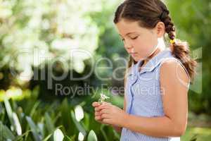 Girl holding flower standing at backyard