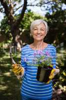 Portrait of smiling senior woman holding potted plant and trowel