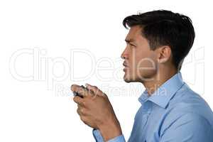 Side view of young businessman playing video game