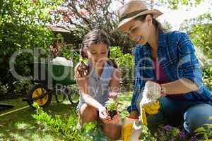Smiling mother teaching daughter to plant seedlings