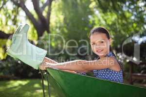 Portrait of girl sitting in wheelbarrow at backyard
