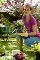 Portrait of smiling woman holding potted plant in backyard