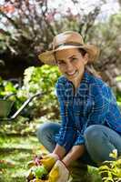 Portrait of smiling woman planting seedling in backyard