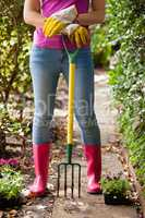 Low section of woman standing with gardening fork on footpath