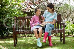 Cheerful mother and daughter reading novel while sitting on bench