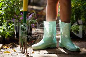 Low section of girl wearing green rubber boot standing with gardening fork on footpath