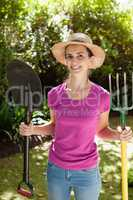 Portrait of smiling beautiful woman holding shovel and gardening fork