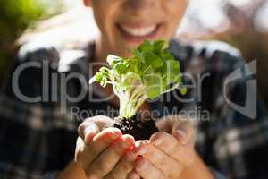 Mid section of smiling woman holding seedling