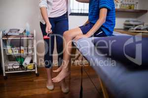 Low section of female therapist hitting boy with reflex hammer on knee