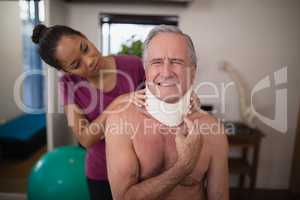 Female therapist looking at senior male patient grimacing with neck collar