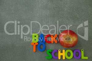 Block letters and apple arranged on chalkboard