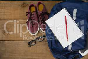 Shoes, spectacles, book, pencil, digital tablet and schoolbag on wooden table