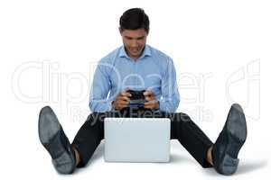 Full length of young businessman playing video game on laptop