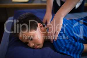 High angle view of boy sleeping on bed while receiving back massage from female therapist