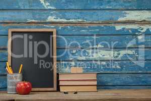 Stack of books, slate, apple and pen holder