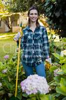 Portrait of smiling woman standing with gardening equipment by hydrangea flowers
