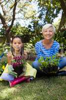 Portrait of smiling granddaughter and grandmother holding plants sitting with crossed legs