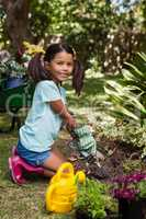 Portrait of smiling girl kneeling while digging soil with trowel