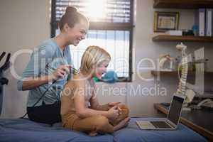 Cheerful female therapist while scanning shoulder of shirtless boy looking at laptop