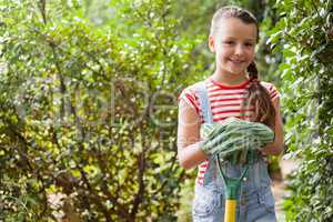 Portrait of smiling girl standing with gardening fork against plants