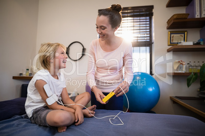 Cheerful female therapist and boy looking at each other with electrical muscle stimulation machine