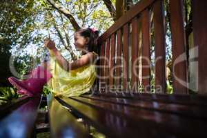 Surface level view of smiling girl using mobile phone while sitting on wooden bench