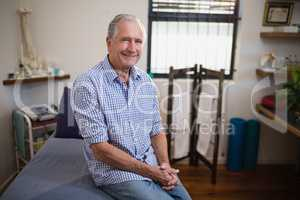 Portrait of smiling senior male patient sitting on bed against window