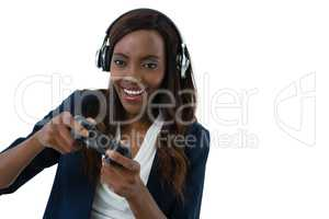 Happy businesswoman playing video game wearing headphones while playing video game