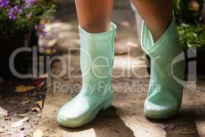 Low section of girl wearing green rubber boot standing on footpath