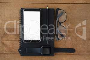 diary, smart watch, pencil, smartphone and spectacles