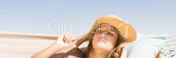 Millennial woman with sun hat asleep on hamoc against Summer sky