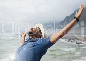 Man with open arms practicing casual mindfulness in front of sea landscape