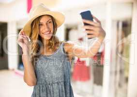Woman taking casual selfie photo in front of shopping mall