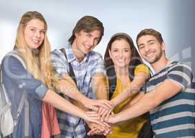 Students joing hands together in front of blurred background