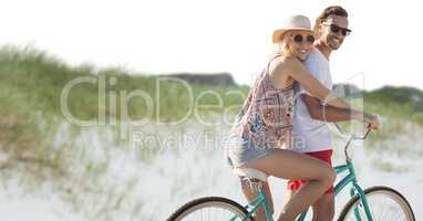 Millennial couple on bicycle against sand dune