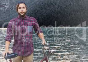 Millennial man with bicycle against river and forest