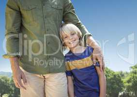 Father arm around son against sky and blurry trees