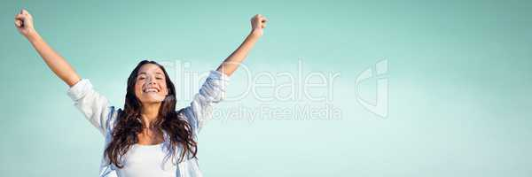Millennial woman with arms in air against  light green background