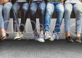 Group of people's legs sitting on bench in front of grey background