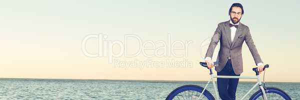 Millennial man with bow tie and bicycle against horizon