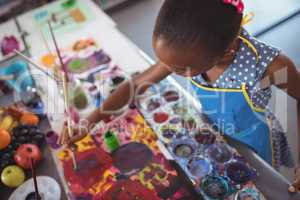 High angle view of focused elementary girl painting at desk