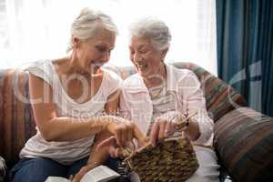 Cheerful senior women talking about knitting while sitting on sofa against window