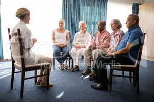 Female doctor sitting with senior people on chairs against window